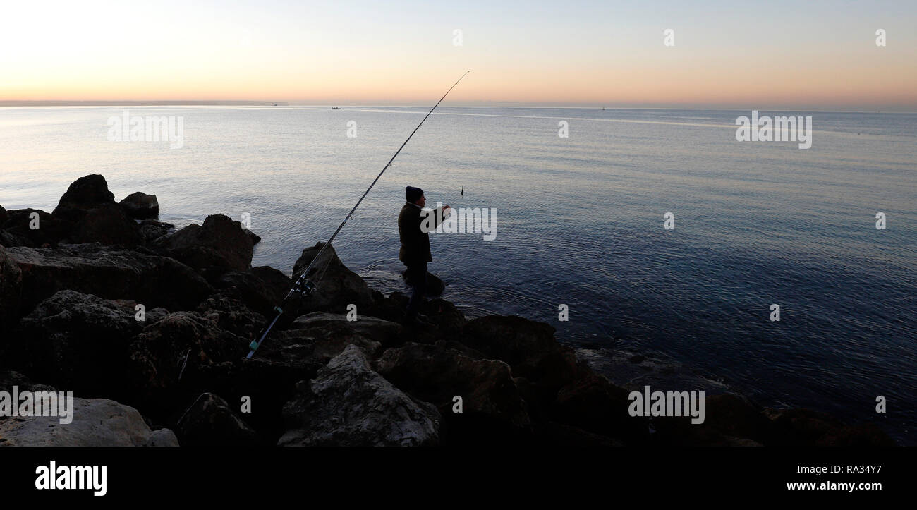 Palma, Spain. 31st Dec, 2018. Manolo from Spain goes fishing whenever he can when the sun comes up, today fishes in Playa de Palma during the sunny morning of the last day of the year. Credit: Clara Margais/dpa/Alamy Live News - Stock Image