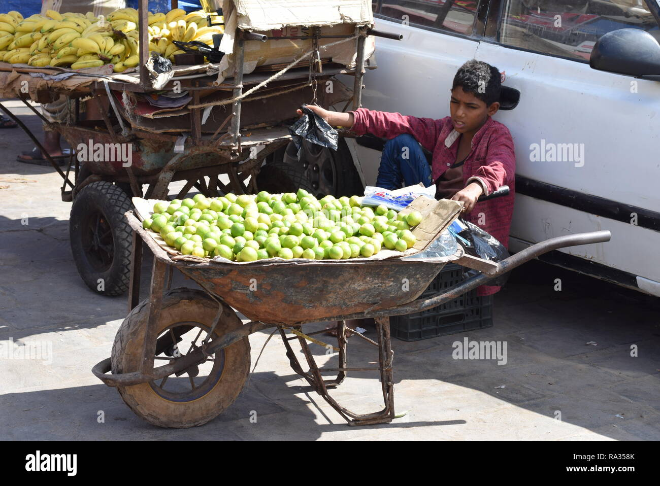 Aden, Yemen. 31st Dec, 2018. A young fruit vender waits for customers in the southern port city of Aden, Yemen, Dec. 31, 2018. In 2018, Yemen experienced dramatic escalation of the internal military conflict, severe collapse of the country's national currency and an outbreak of acute diseases. Yemeni people also suffered skyrocketing prices of basic commodities and lack of basic services, including clean water and electricity. TO GO WITH Spotlight: Yemenis to receive new year amid hard challenges, devastating civil war Credit: Murad Abdo/Xinhua/Alamy Live News - Stock Image