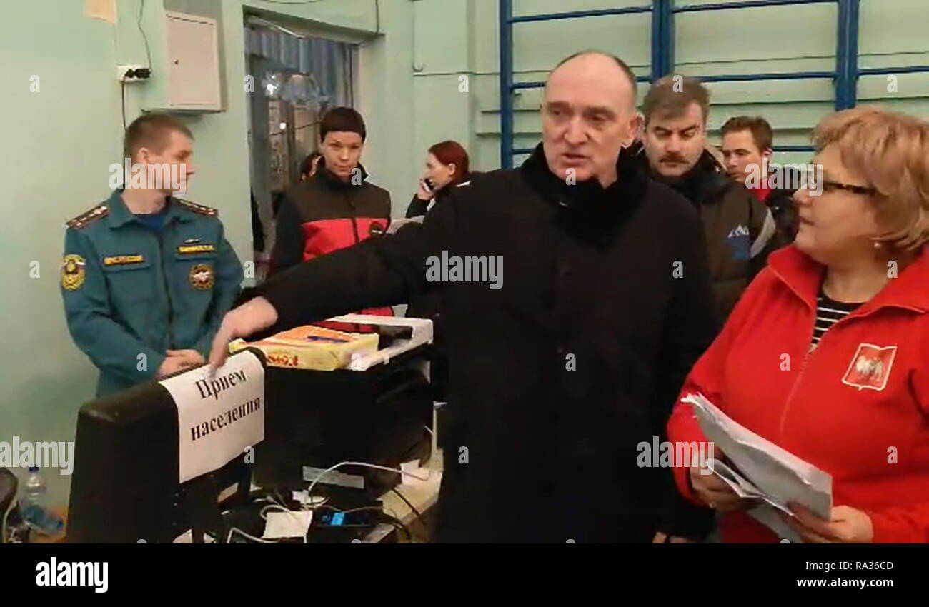Magnitogorsk, Russia. 31st Dec, 2018. Magnitogorsk, Russia. 31st Dec, 2018. Chelyabinsk Region Governor Boris Dubrovsky (C) in a school temporarily housing the victims of an apartment building collapse in the city of Magnitogorsk. A domestic gas blast has caused a partial collapse of a residential building at 164 Karla Marksa Avenue; 4 people have been killed, dozens remain missing. The Chelyabinsk Region Branch of the Russian Emergencies Ministry/TASS Credit: ITAR-TASS News Agency/Alamy Live News - Stock Image