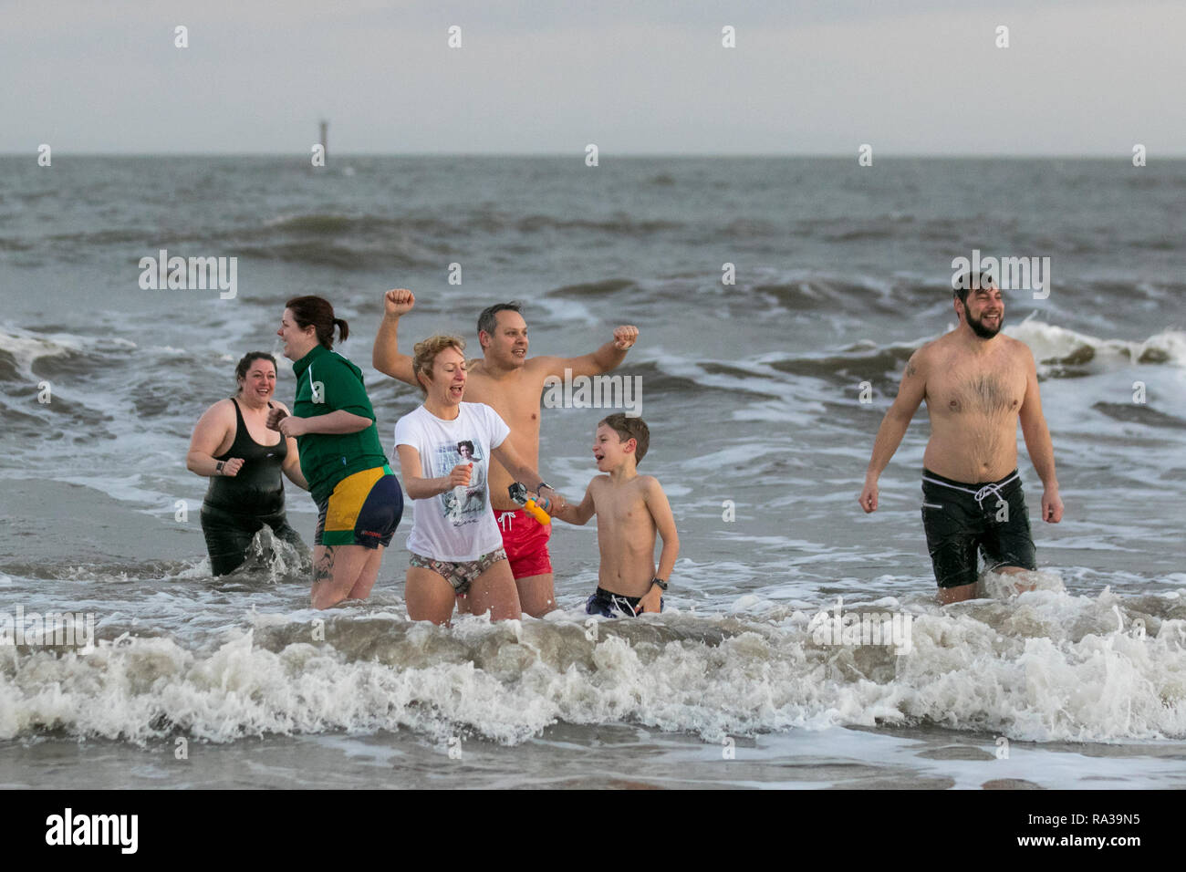 Fleetwood, Lancashire, UK. 1st Jan 2019. New Year's Day Swim. Organised by Fleetwood Kite Club, the New Year's Day Dip is a fairly new tradition in Fleetwood. It started in the 1990's and is growing every year.  There are no rules other than no wetsuits allowed. There's no minimum time of how long you have to stay in the sea for – other than you have to get wet!  Credit: MediaWorldImages/AlamyLiveNews. - Stock Image
