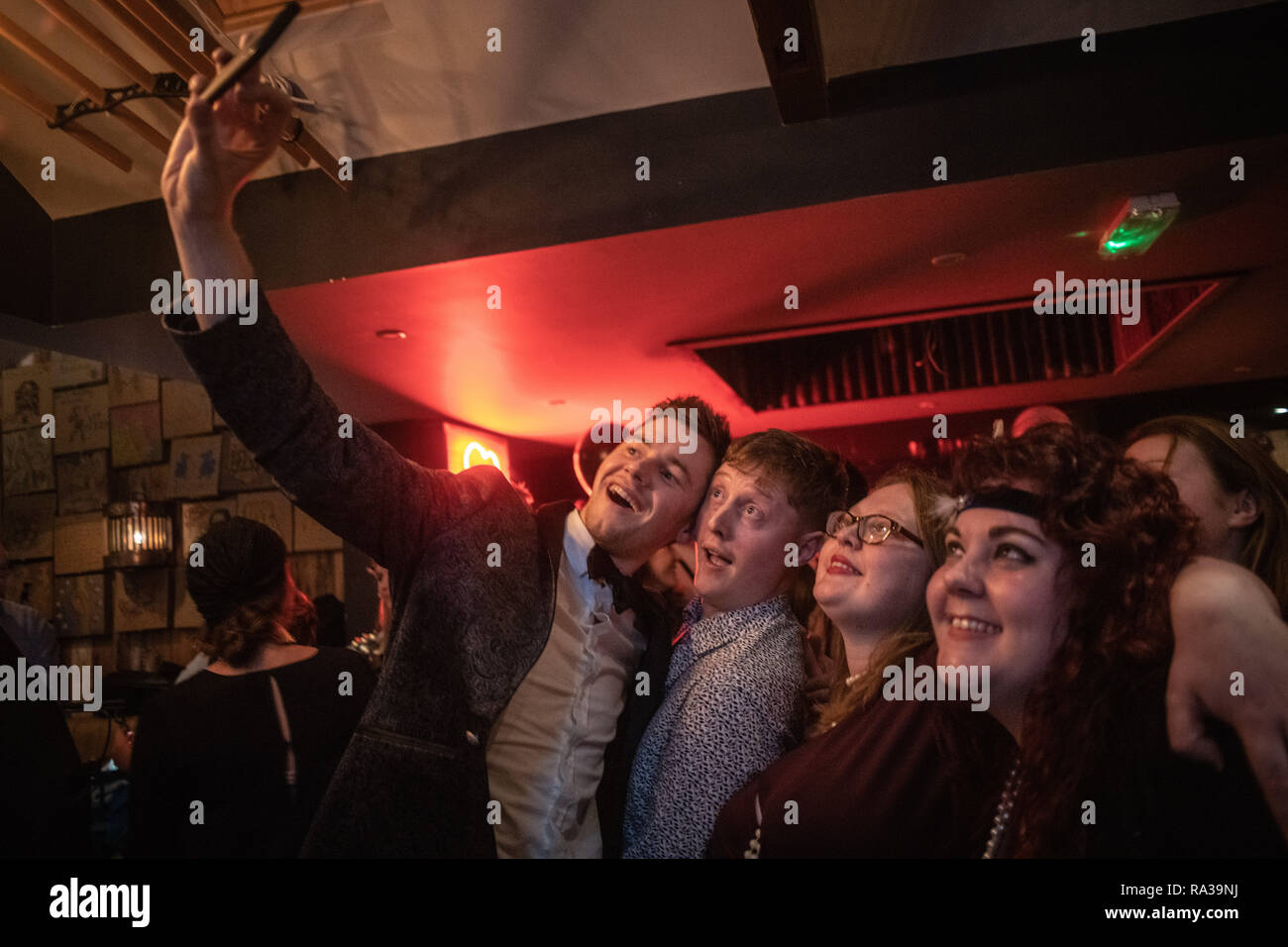 Oxford, UK. 31st Dec, 2018. New Year's Eve party in Oxford. The Rickety Press through a celebration of the 1920s, complete with blacked out windows and a performance by the Rabbit Foot Spasm band. Dressed up and getting a selfie at midnight. Permission given for pictures to be published. Credit: Sidney Bruere/Alamy Live News Stock Photo