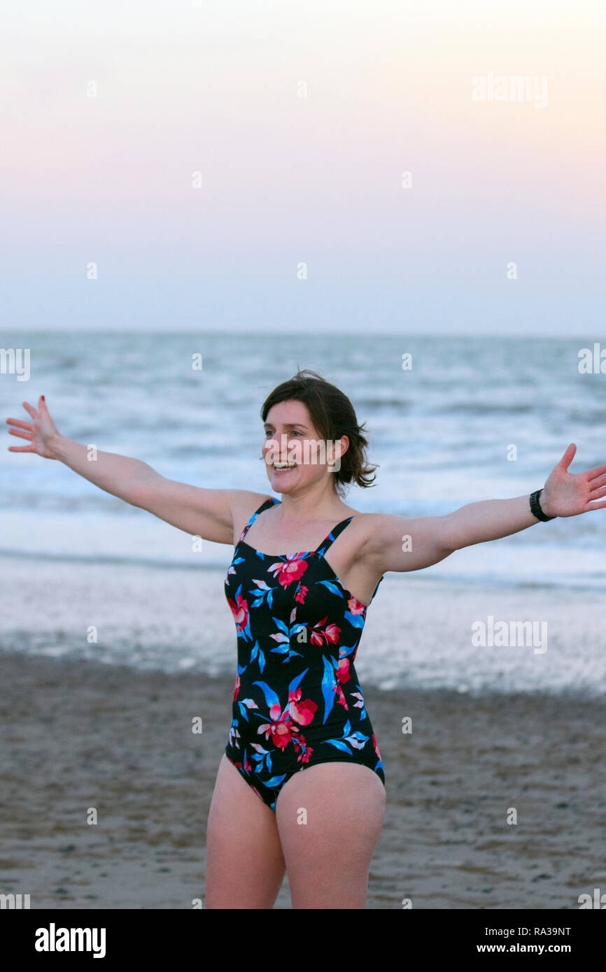 Fleetwood, Lancashire, UK. 1st Jan 2019. Naomi celebrates after a New Year's Day Swim. Organised by Fleetwood Kite Club, the New Year's Day Dip is a fairly new tradition in Fleetwood. It started in the 1990's and is growing every year.  There are no rules other than no wetsuits allowed. There's no minimum time of how long you have to stay in the sea for – other than you have to get wet!  Credit: MediaWorldImages/AlamyLiveNews. - Stock Image