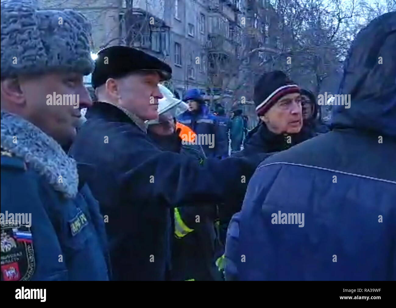 Magnitogorsk, Russia. 01st Jan, 2019. MAGNITOGORSK, RUSSIA - JANUARY 1, 2019: Chelyabinsk Region Governor Boris Dubrovsky (2nd L) at the site of an apartment block collapse. On December 31, 2018, a domestic gas explosion caused a partial collapse of the residential building at 164 Prospekt Karla Marksa Street killing eight people and leaving dozens missing. Video Screen Grab/Press Office of the Chelyabinsk Region Governor/TASS Credit: ITAR-TASS News Agency/Alamy Live News - Stock Image