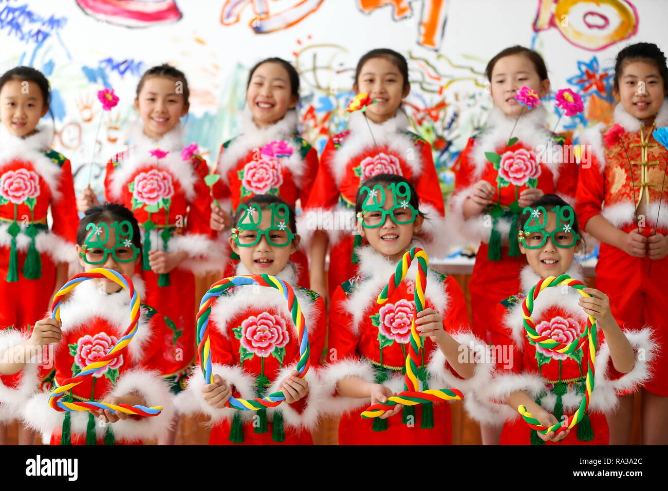 Qingdao, China's Shandong Province. 1st Jan, 2019. Pupils dressed in festive costumes pose for a group photo in Qingdao, east China's Shandong Province, Jan. 1, 2019. Various activities were organized across China to greet the year of 2019. Credit: Liang Xiaopeng/Xinhua/Alamy Live News - Stock Image