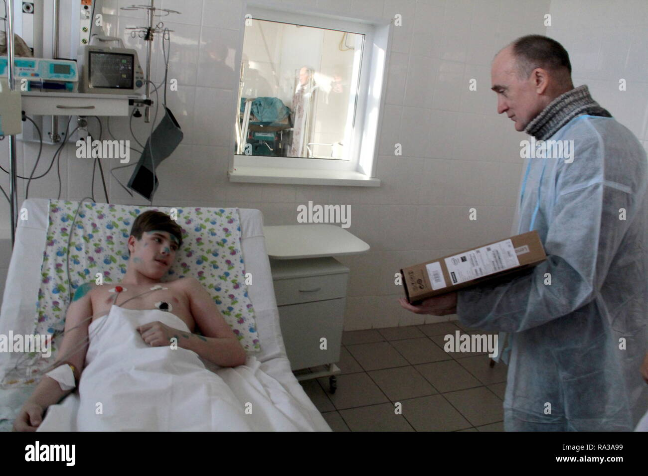Magnitogorsk, Russia. 01st Jan, 2019. MAGNITOGORSK, RUSSIA - JANUARY 1, 2019: Chelyabinsk Region Governor Boris Dubrovsky (R) visits Sergei Gavrilov injured in an apartment block collapse at a hospital. On December 31, 2018, a domestic gas explosion caused a partial collapse of a residential building at 164 Prospekt Karla Marksa Street killing eight people and leaving dozens missing. Ilya Moskovets/TASS Credit: ITAR-TASS News Agency/Alamy Live News - Stock Image