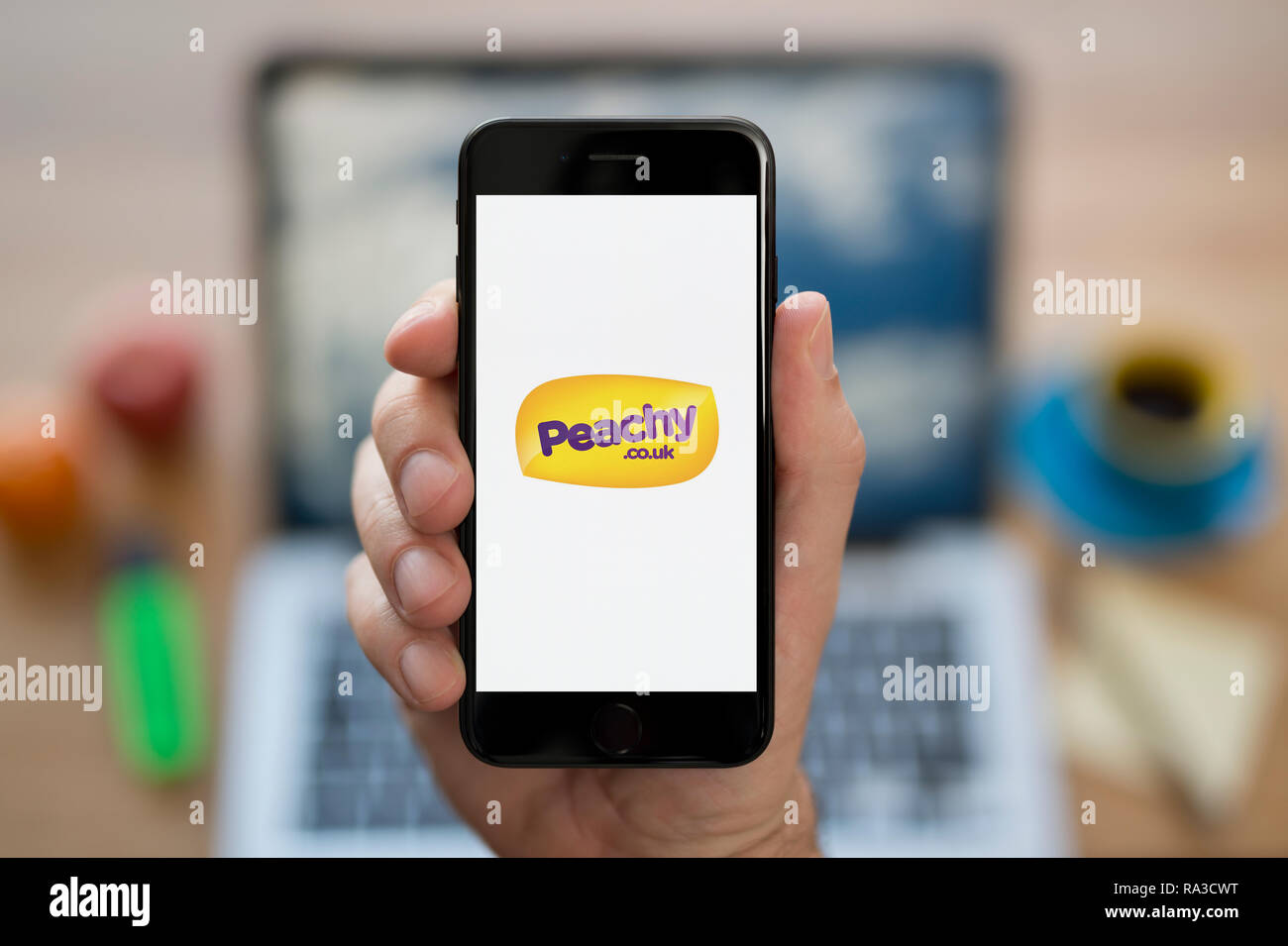 A man looks at his iPhone which displays the Peachy logo (Editorial use only). - Stock Image