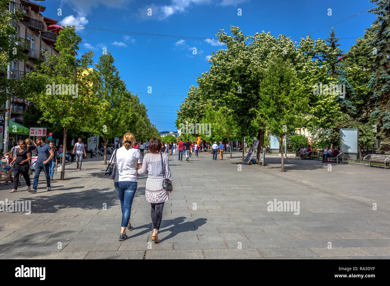 Pristina, Kosovo - May 30th 2018 - Big group of people walking in a wide pavement with big green trees and blue sky in Pristina, capital of Kosovo Stock Photo