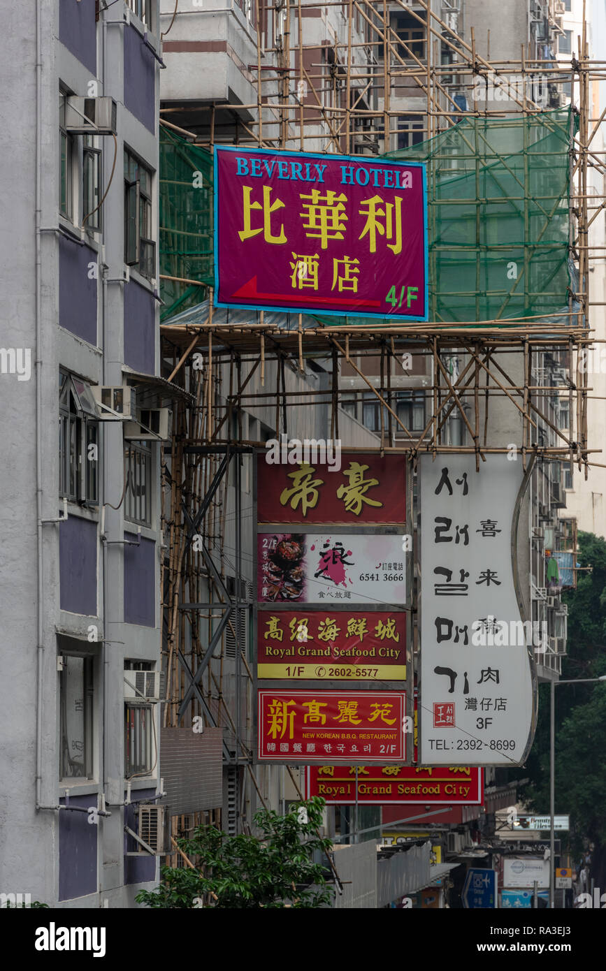 Advertising hoardings and bamboo scaffolding compete for space on the buildings of Lockhart Road in Hong Kong's Wan Chai district - Stock Image