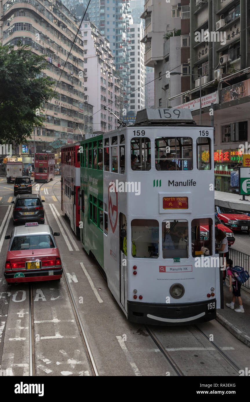 Colourful trams stop at the Fleming Road tram stop in Wan Chai with towering apartment blocks all around in this densely packed district of Hong Kong Stock Photo