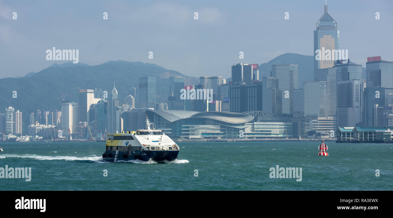 The Hong Kong & Kowloon Ferries catamaran, 'Sea Superb', navigating Victoria harbour with the spectacular backdrop of Hong Kong Island's skyscrapers - Stock Image