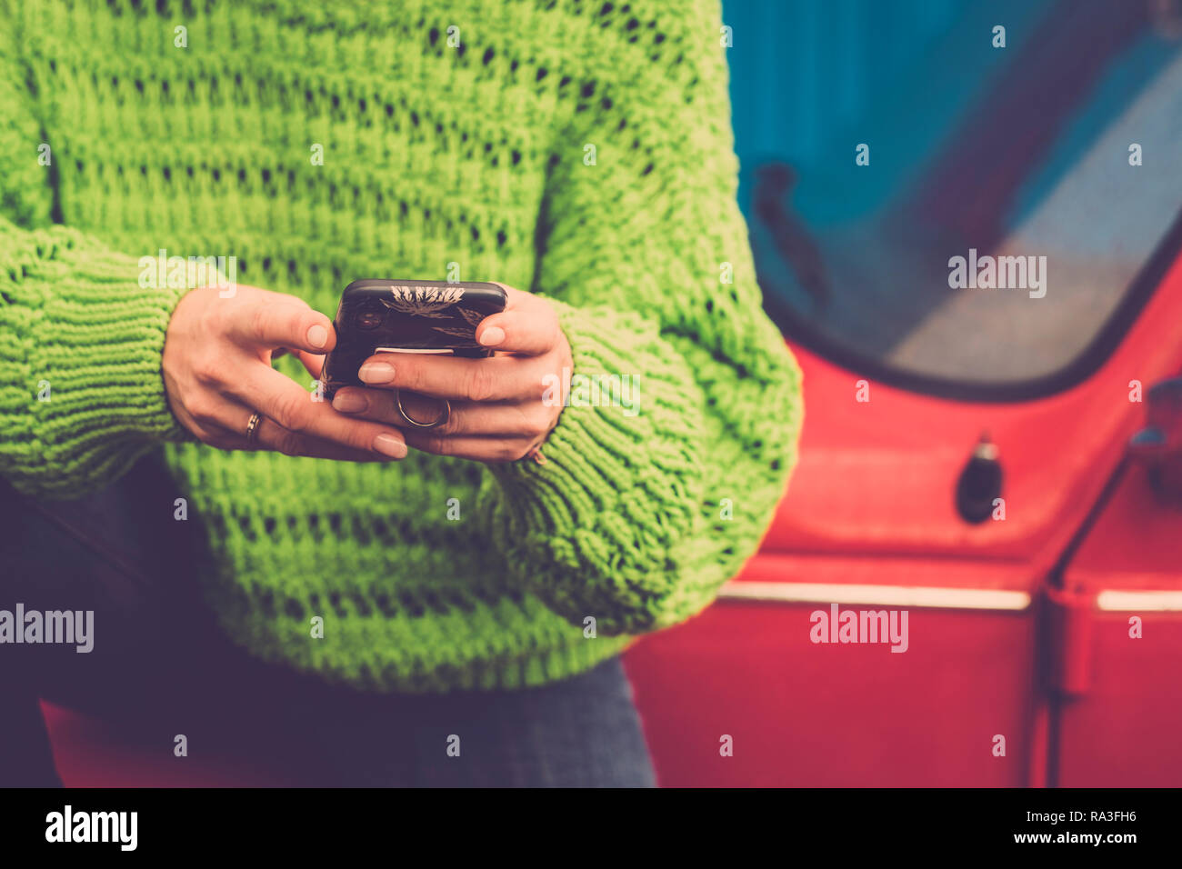 Close-up female hands using and messaging with modern technology smart phone - green jackets and red old vintage car in background - coloured lifestyl - Stock Image