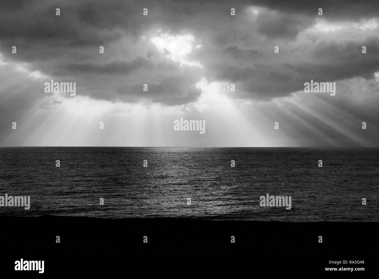 black and white photograph of lots of long beams of sunlight shining through dramatic clouds casting long rays of light onto the sea making the sea gl - Stock Image