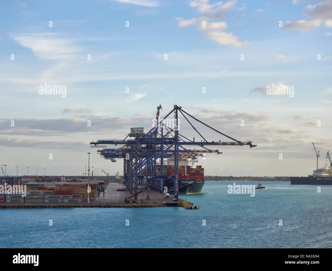 The Container Terminal at Freeport in the Bahamas, with a Container shipped berthed alongside on one early November Morning. - Stock Image