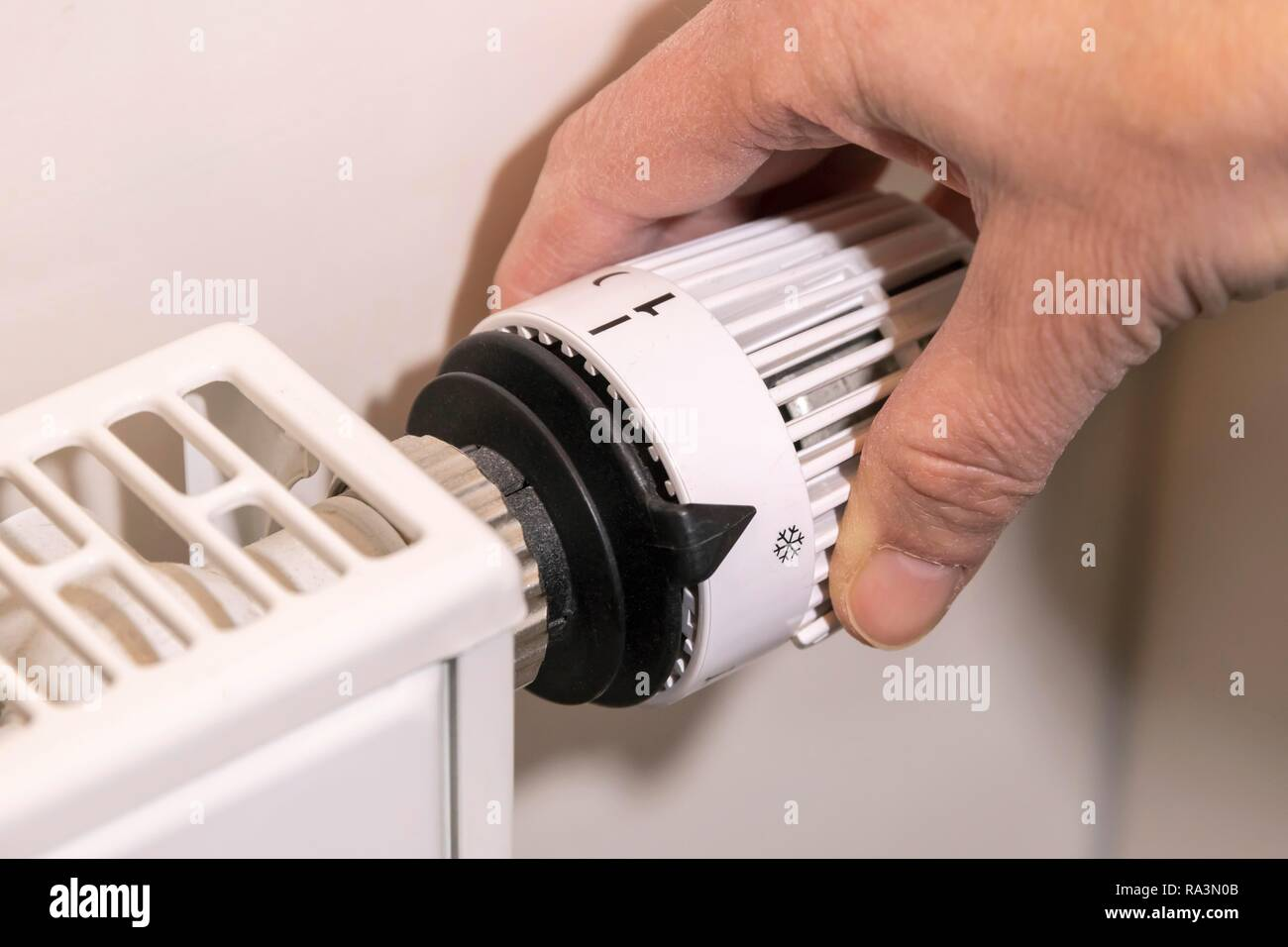 Hand adjusts the temperature at a thermostat of the heating, Bavaria, Germany - Stock Image