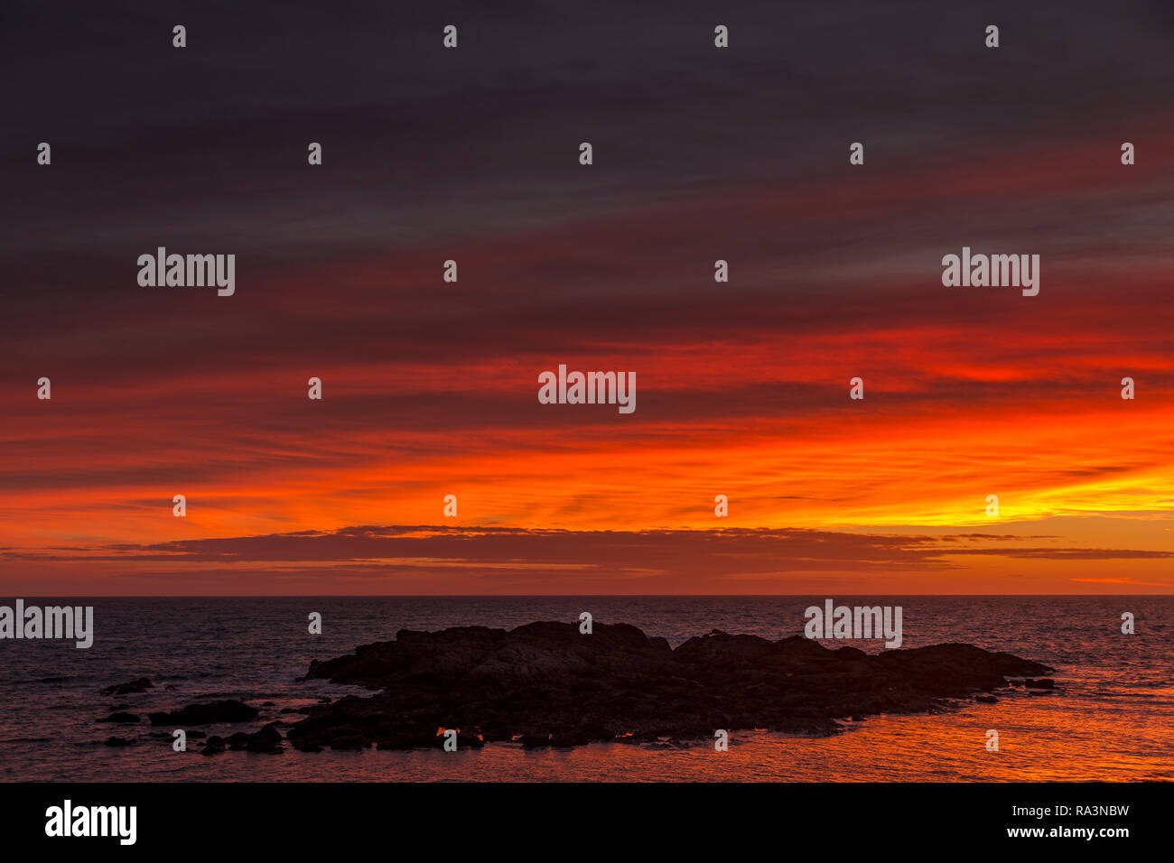 Sunset over the sea from Trearddur on the coast of Anglesey, North Wales - Stock Image