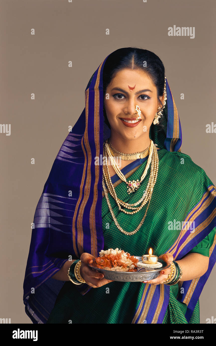 A PORTRAIT OF A MARATHI/MAHARASHTRIAN Bride dressed in traditional SAREE, HOLDING A PUJA THALI/ CEREMONIAL VESSEL WITH A LIT LAMP. Stock Photo