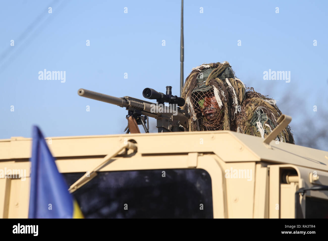 Bucharest, Romania - December 1, 2018: Romanian army sniper, armed with the US M110 semi-automatic sniper rifle and on top of a Humvee armored vehicle - Stock Image