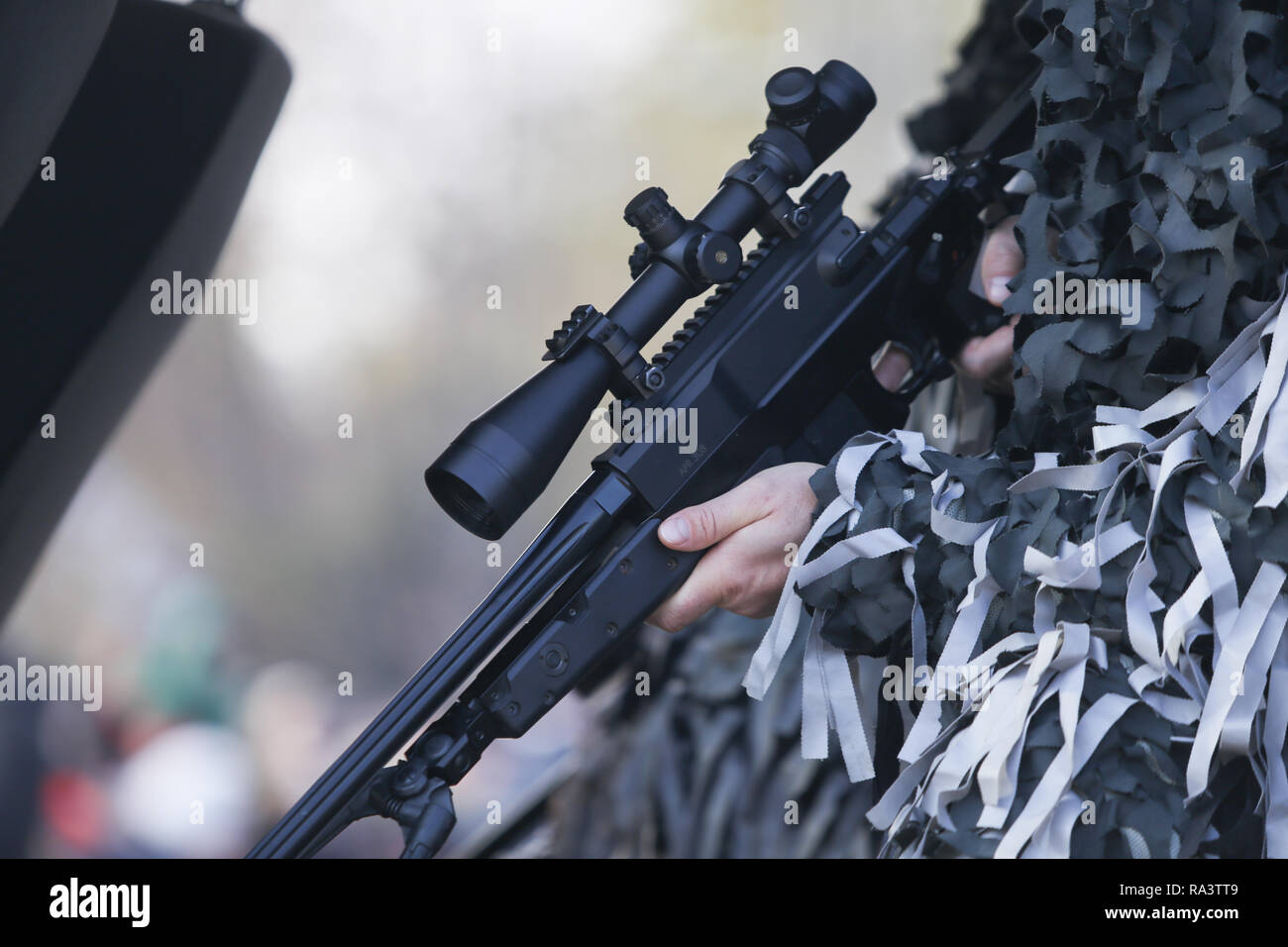 Details with the hands of an army sniper holding his rifle - Stock Image