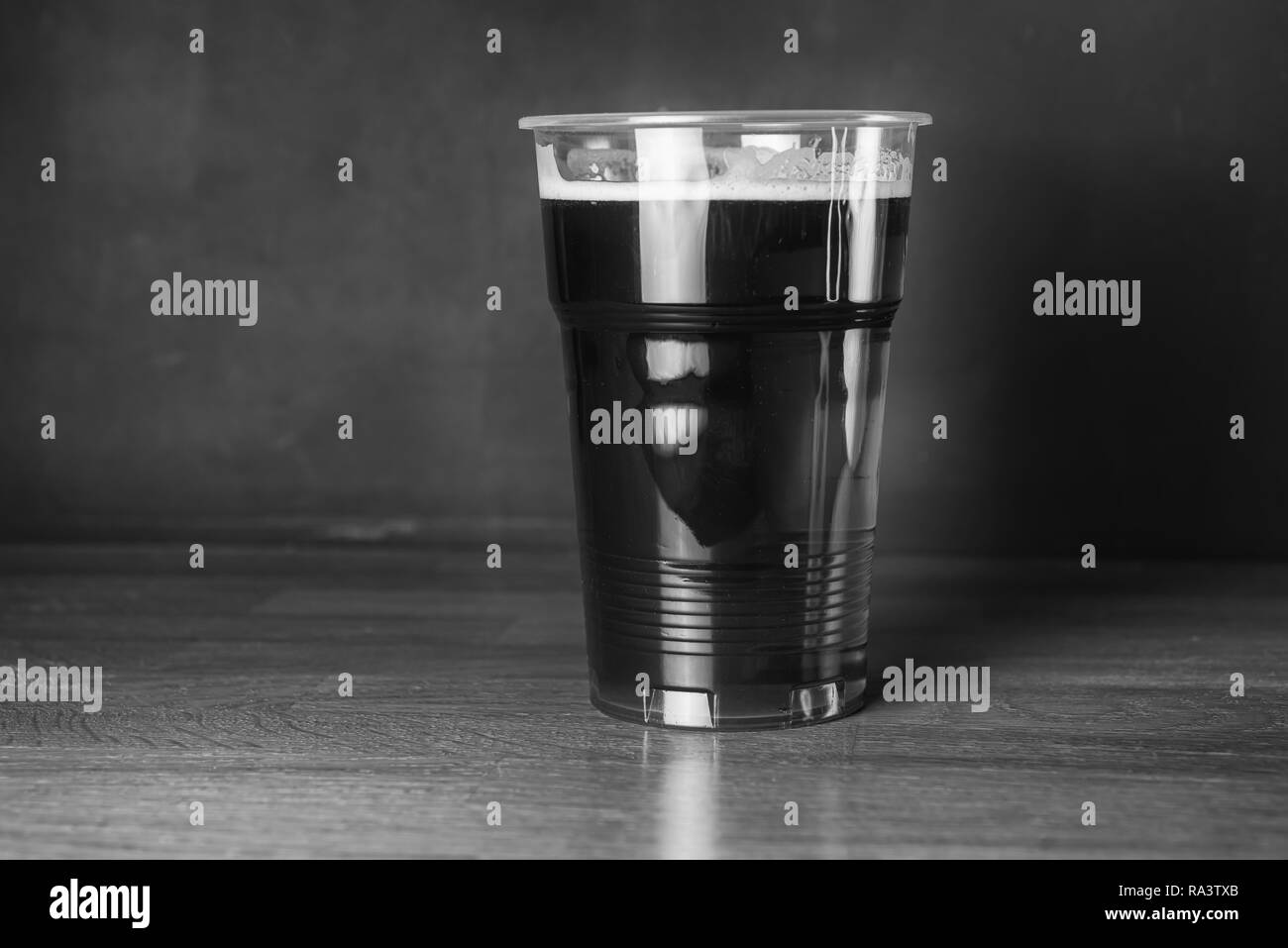 Vintage black and white photography. A glass of cheap craft beer in pub or bar - Stock Image