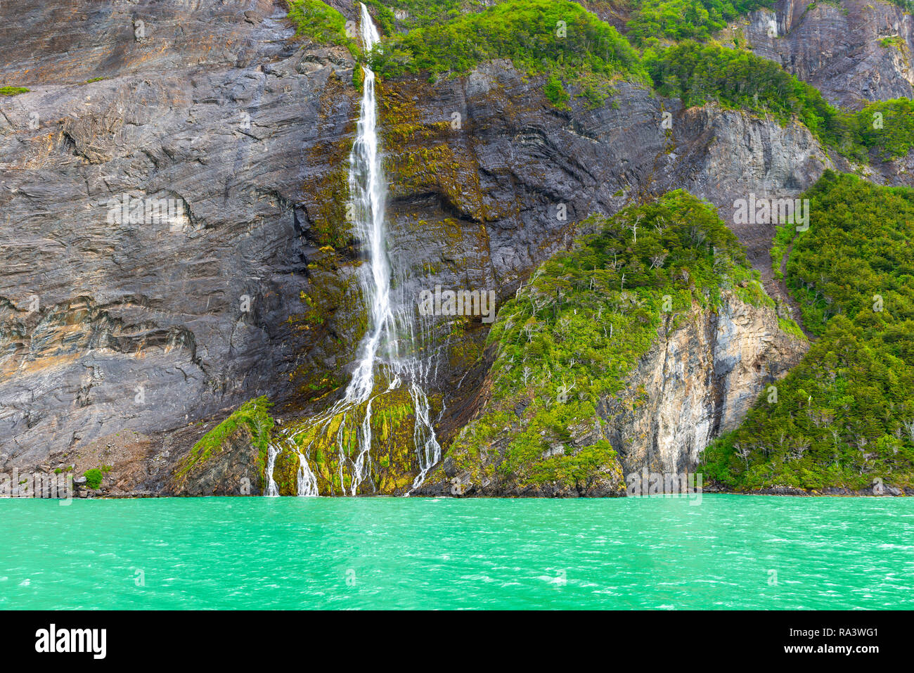 The turquoise fjord of the Last Hope with a waterfall along a cliff near the Torres del Paine national park, Patagonia, Chile. - Stock Image