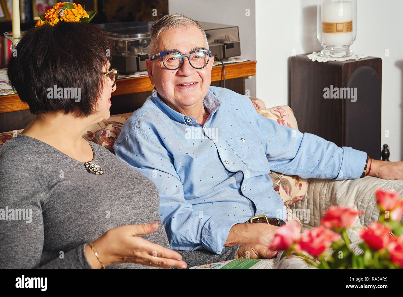 happy seniors couple sitting on the couch in a floral pattern at home - Stock Image