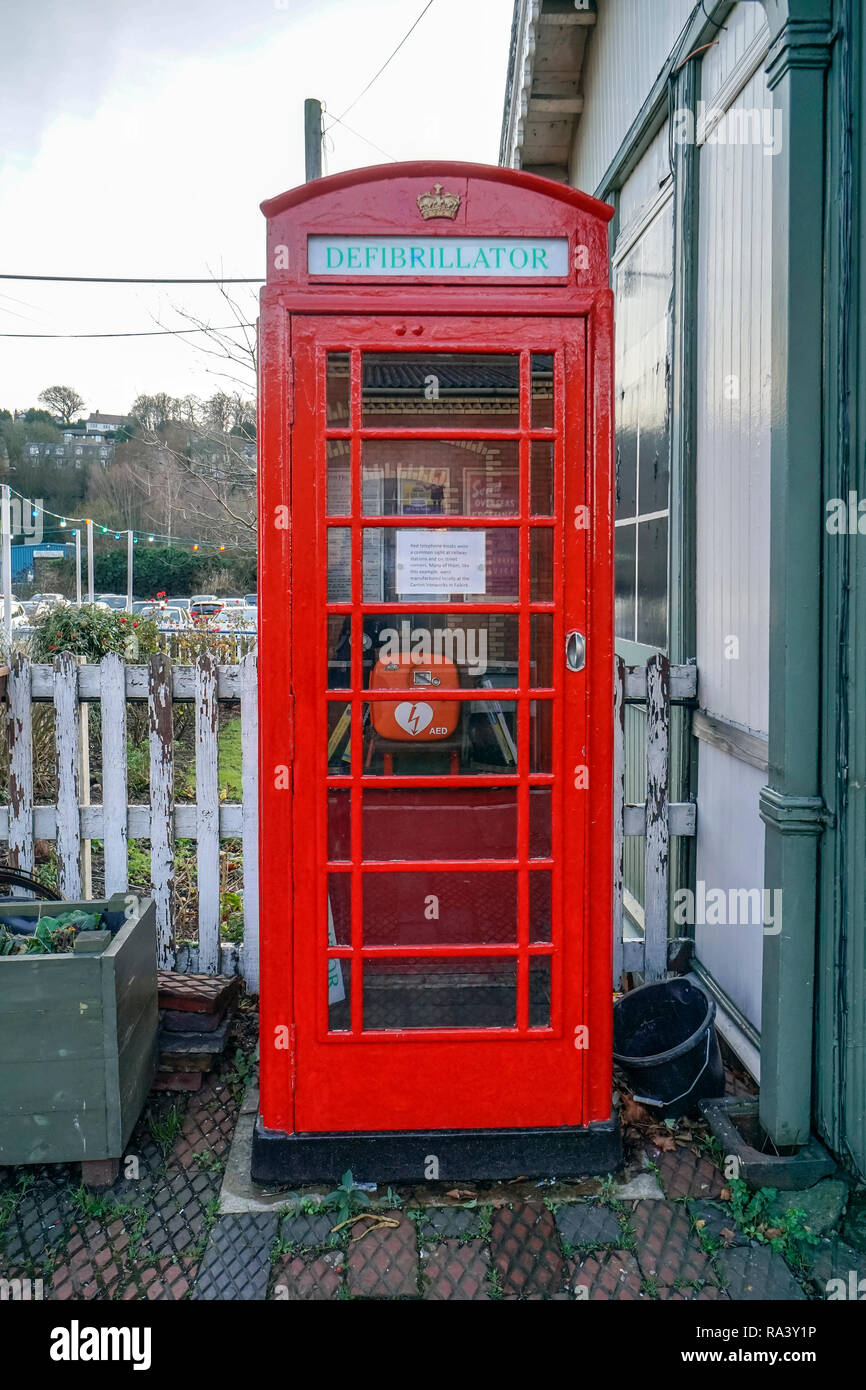 Old red telephone box with a defibrillator inside on the platform at Bo'ness & Kinneil Railway in Bo'ness Falkirk district Scotland UK - Stock Image