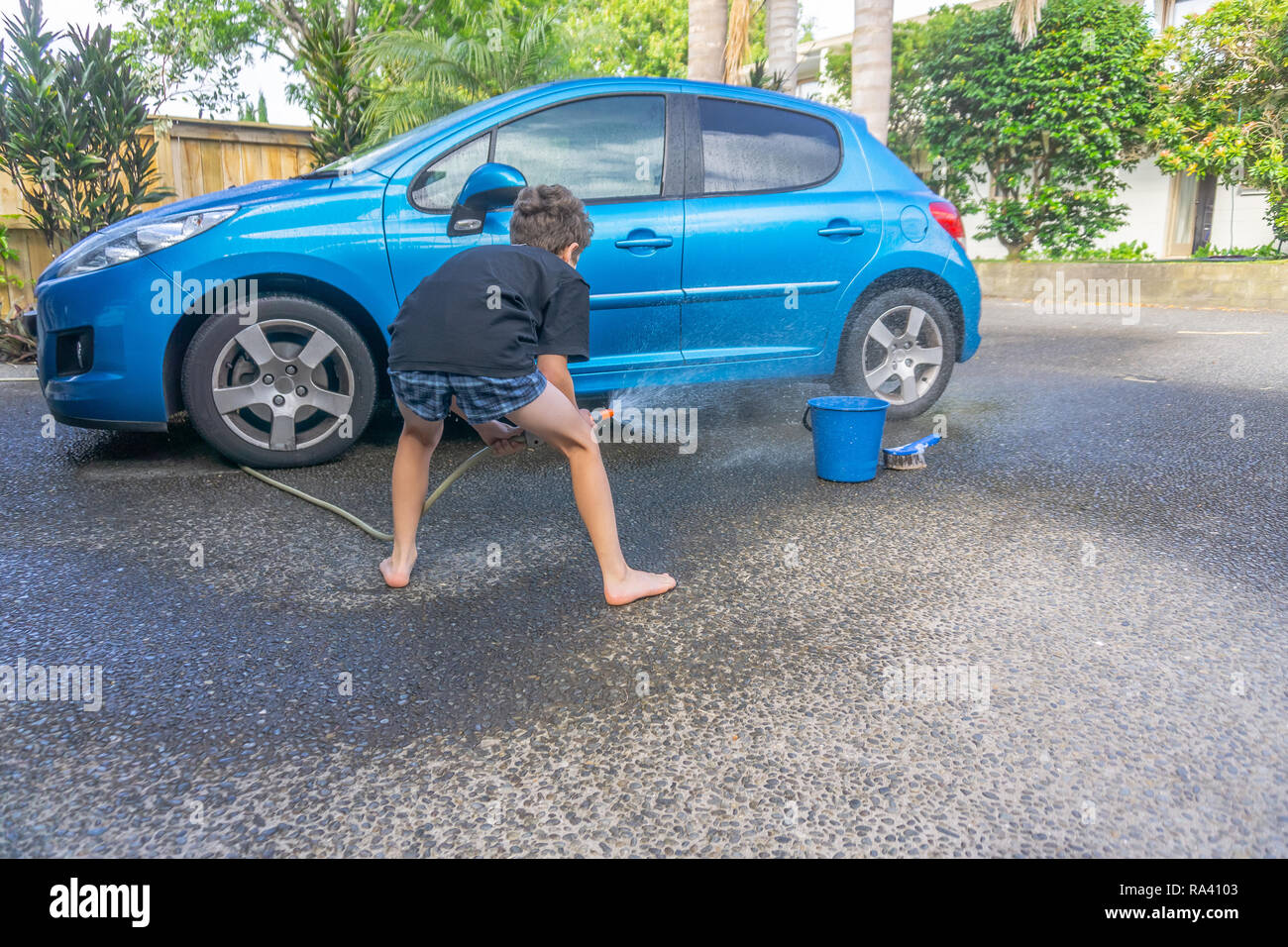 Boy earning pocket money cleaning blue compact car with hose, bucket of water and car brush - Stock Image