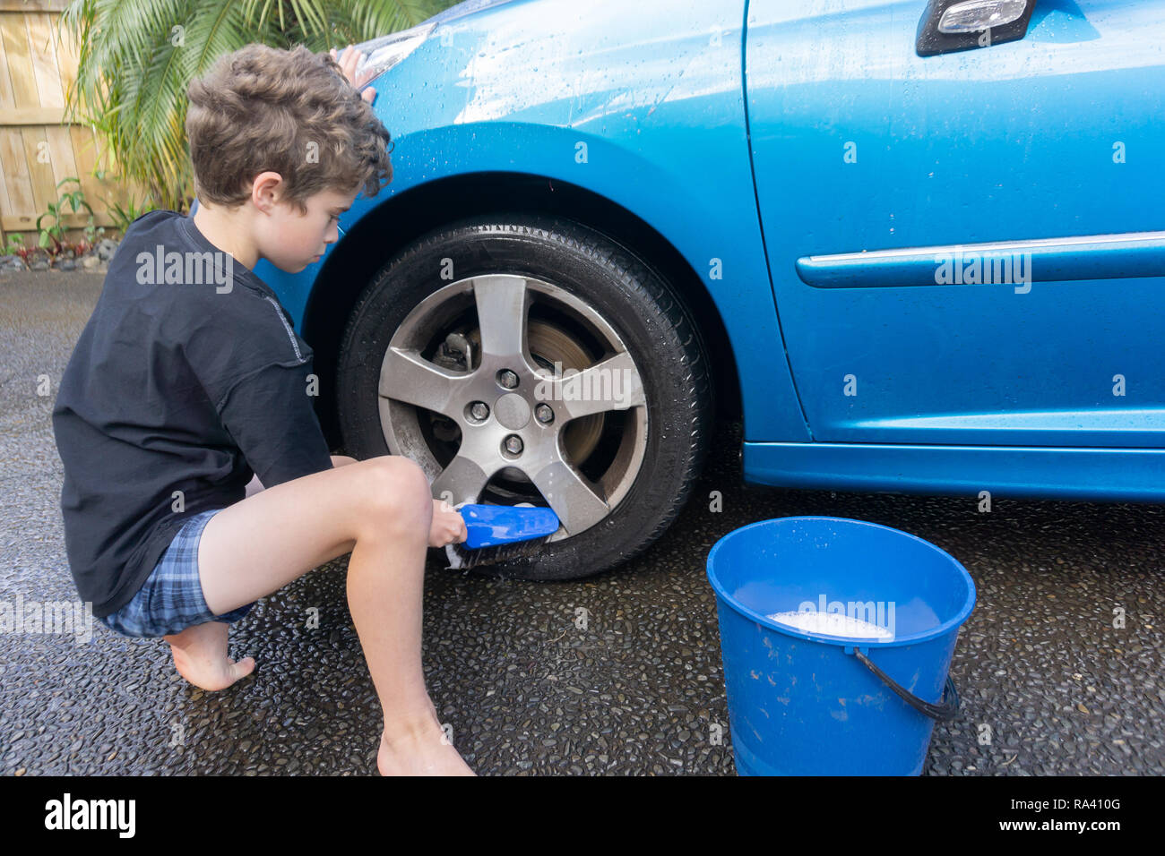 Boy earning pocket money cleaning blue compact car with hose, bucket of water and car brush cleaning wheels. - Stock Image