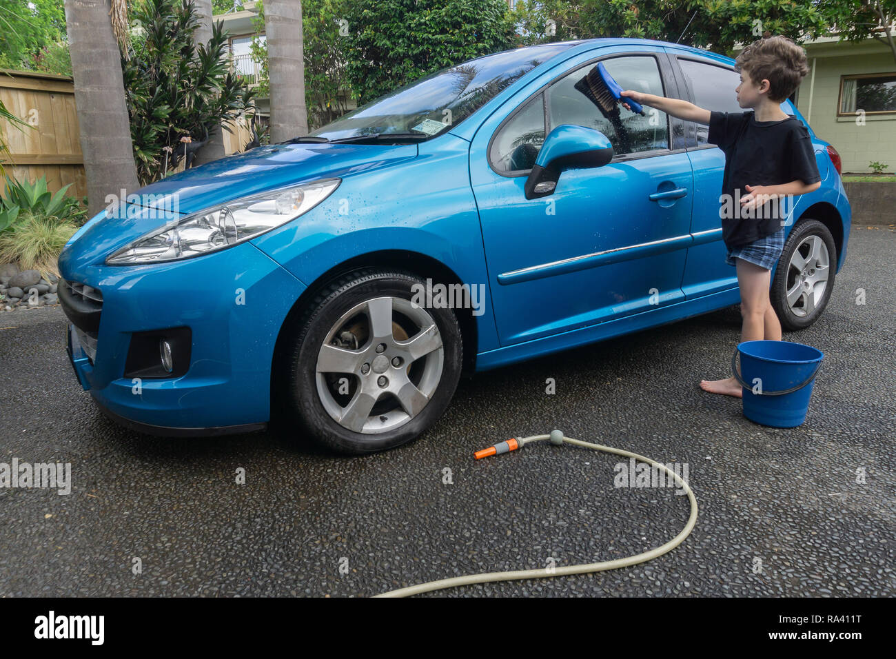 Boy earning pocket money cleaning windows of blue compact car with hose, bucket of water and car brush - Stock Image