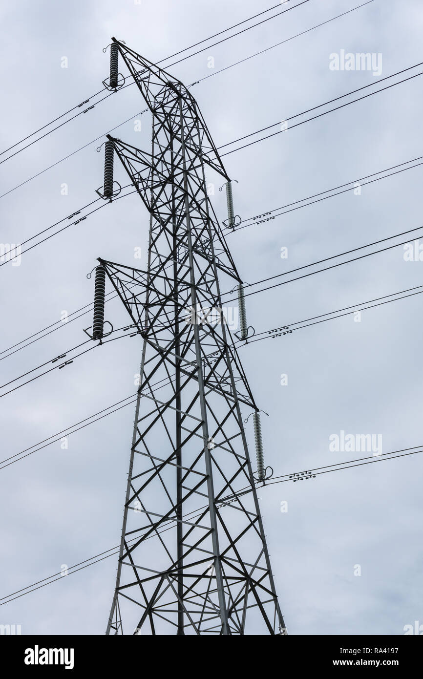 Electricity pylon and overhead power lines looking upwards towards the top of the steel tower. Stock Photo