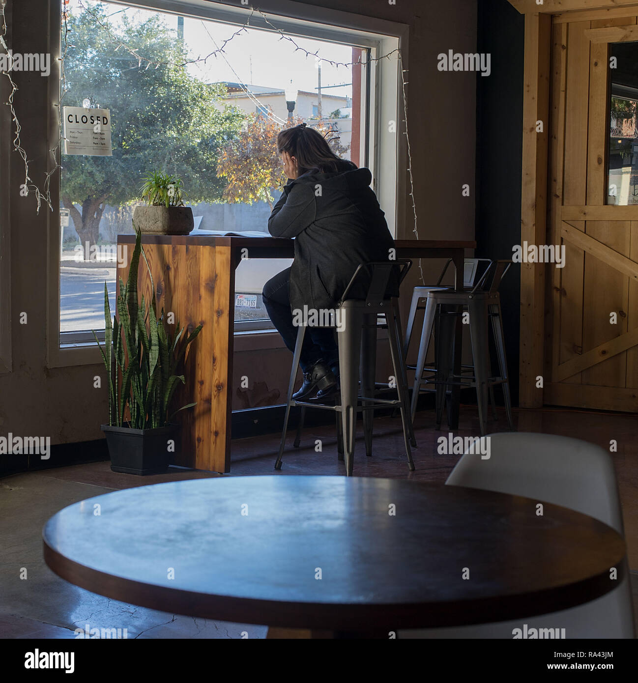 Woman in a coffee shop looking through a window - Stock Image