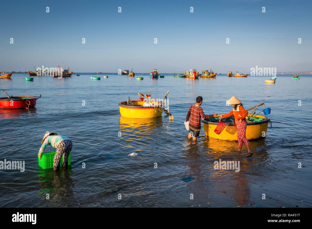 fishermen village in Phan Thiet Vietnam. Traditional Vietnamese boats in fishing port and fishermen trading fish products in the fishing village - Stock Image