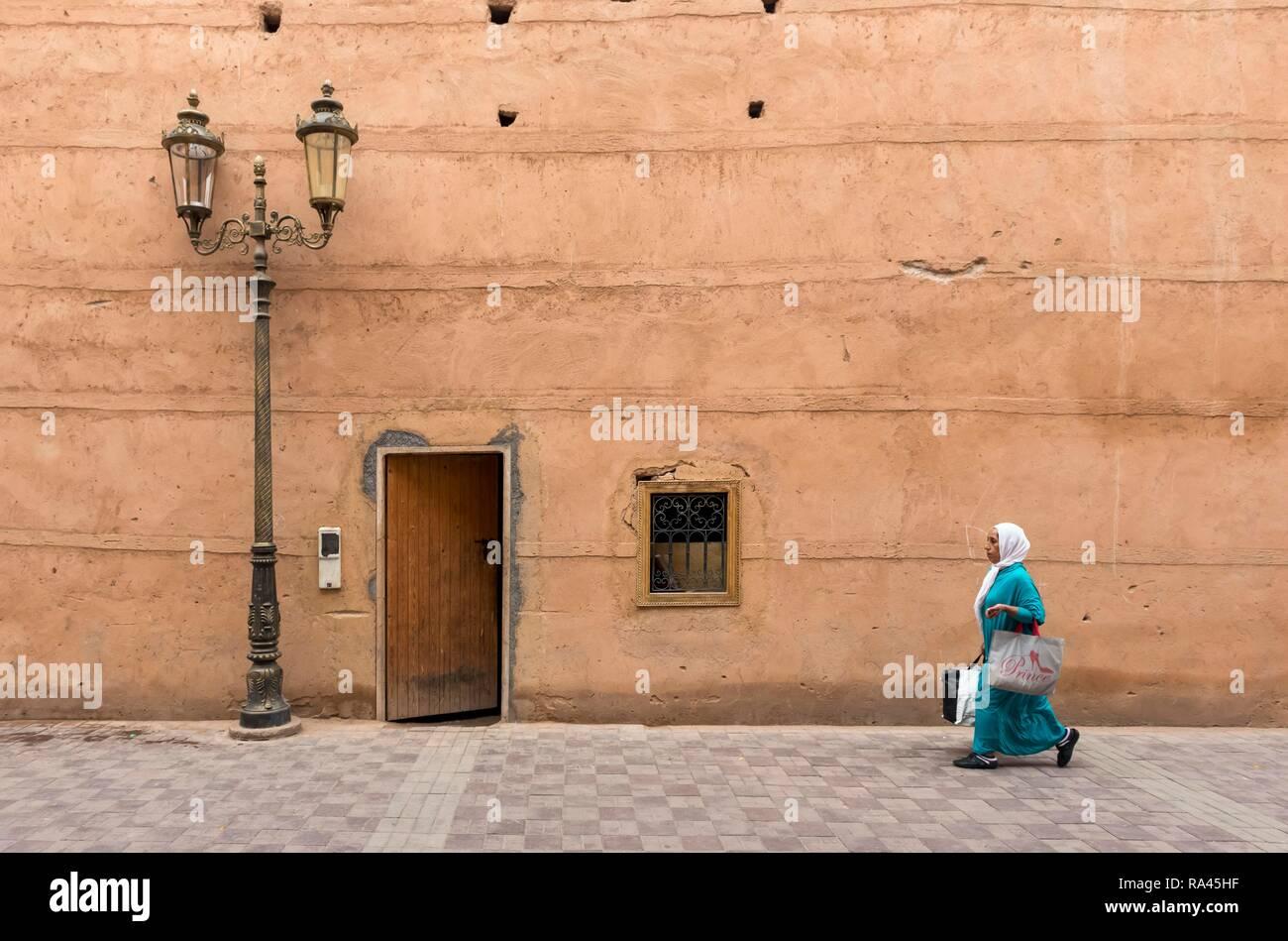 Woman walks along clay walls of Badi Palace in Marrakech, Morocco Stock Photo