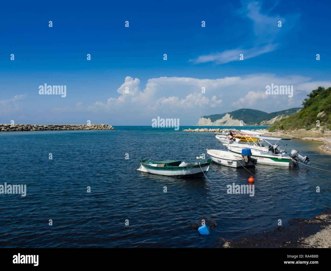 Pleasure boats moored off Kassiopi beach on the Greek island of Corfu Greece. - Stock Image