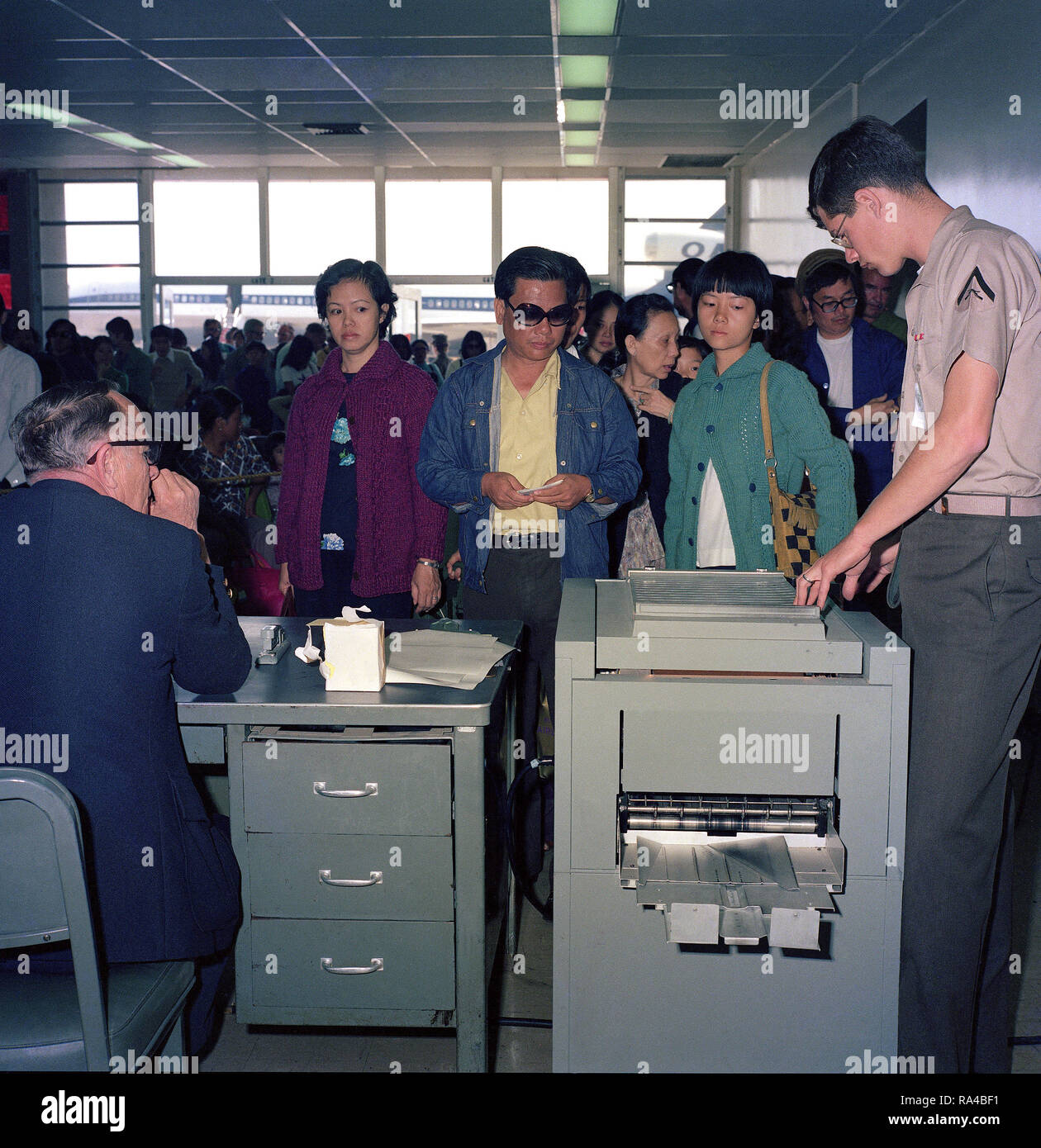 1975 - Vietnamese refugees evacuated from Saigon are processed at the air station passenger terminal before departing for Marine Corps Base, Camp Pendleton. Stock Photo