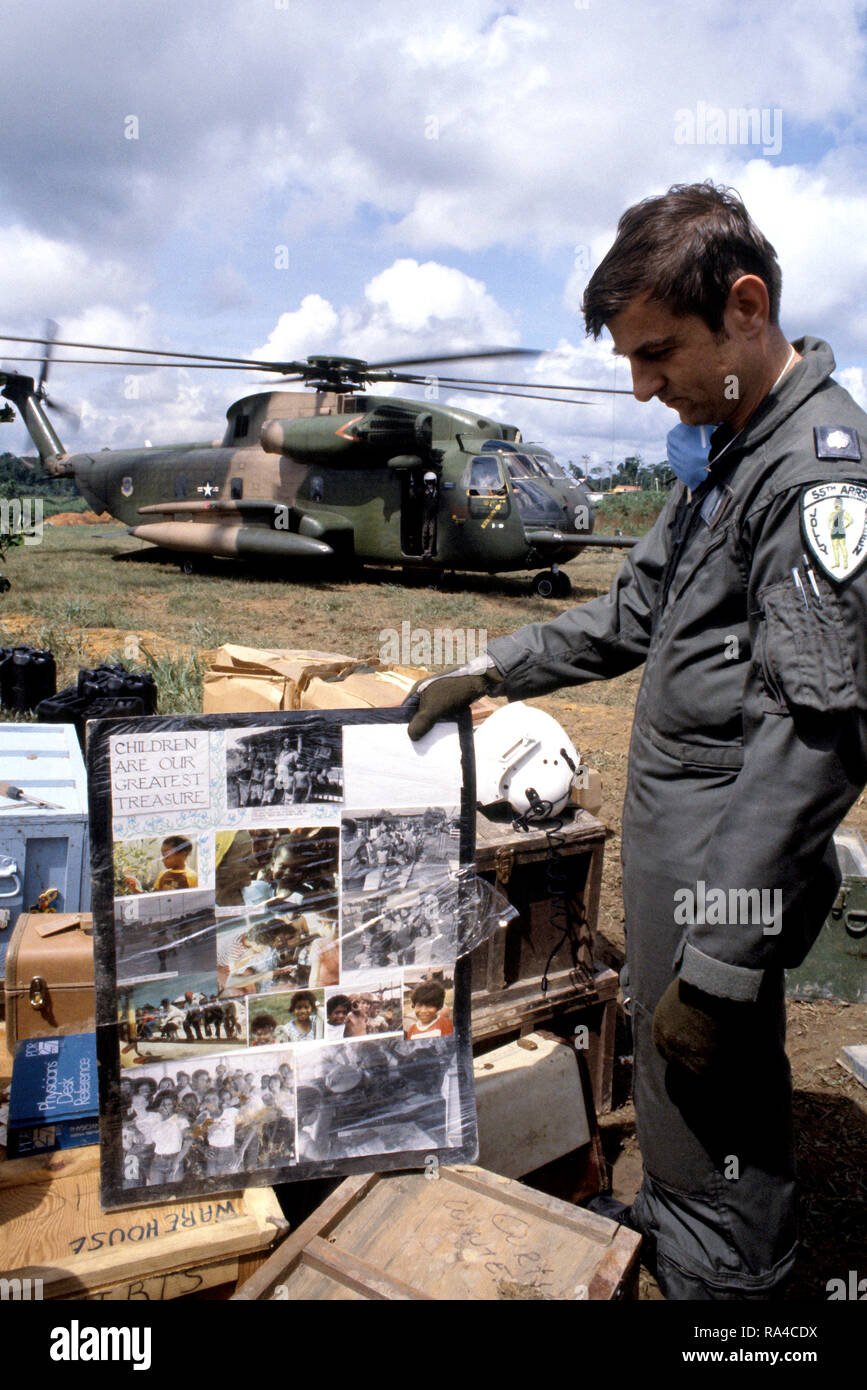 1978 - Lieutenant Colonel (LTC) Leonard Morrisey, an HH-53 Jolly Green Giant helicopter pilot from the 55th Aerospace Rescue and Recovery Squadron, examines a poster found at the compound as the remains of the victims of the Jonestown tragedy are loaded aboard the helicopter. - Stock Image