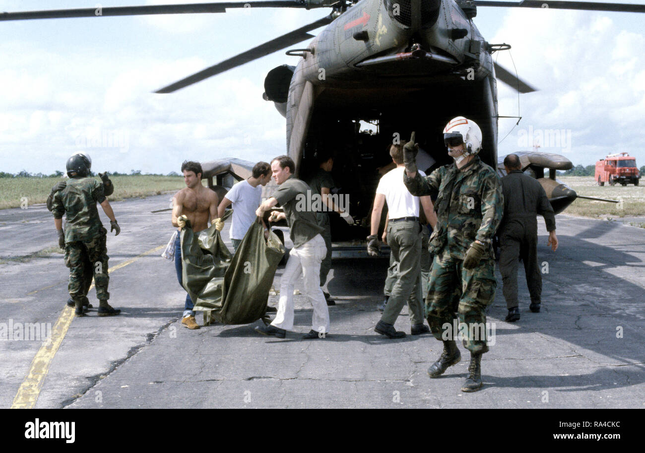 1978 - US military personnel and volunteers offload the remains of Jonestown victims from a 55th Aerospace Rescue and Recovery Squadron HH-53 Jolly Green Giant helicopter.  The bodies will be placed in coffins for transport to Dover Air Force Base, Delaware. - Stock Image