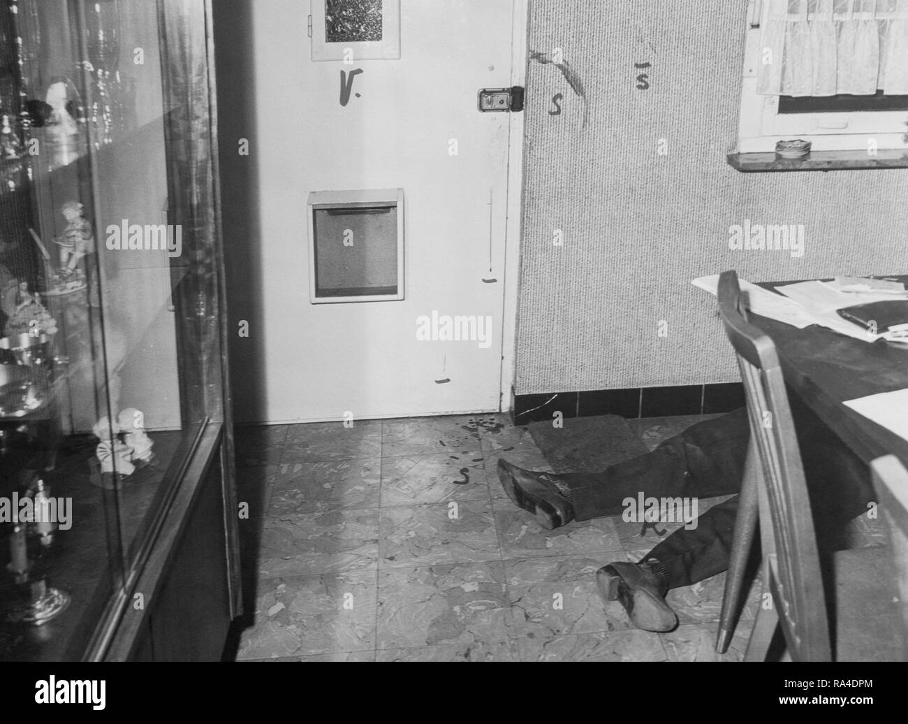 Twentieth century black and white forensic photo of crime scene showing blood stains and corpse of murdered man lying on the ground inside house - Stock Image