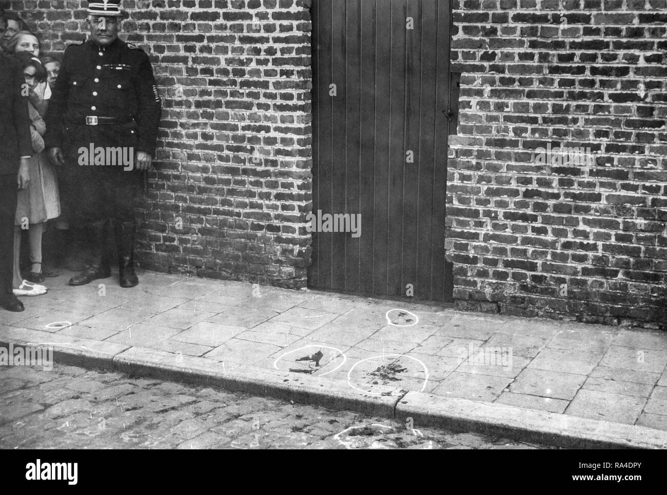 Mid twentieth century black and white photo showing police officer / gendarme and marked blood stains at crime scene on pavement - Stock Image