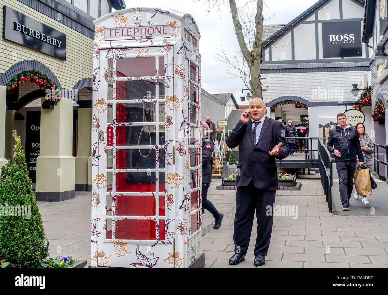 A man uses a mobile phone next to a public phonebox - Stock Image