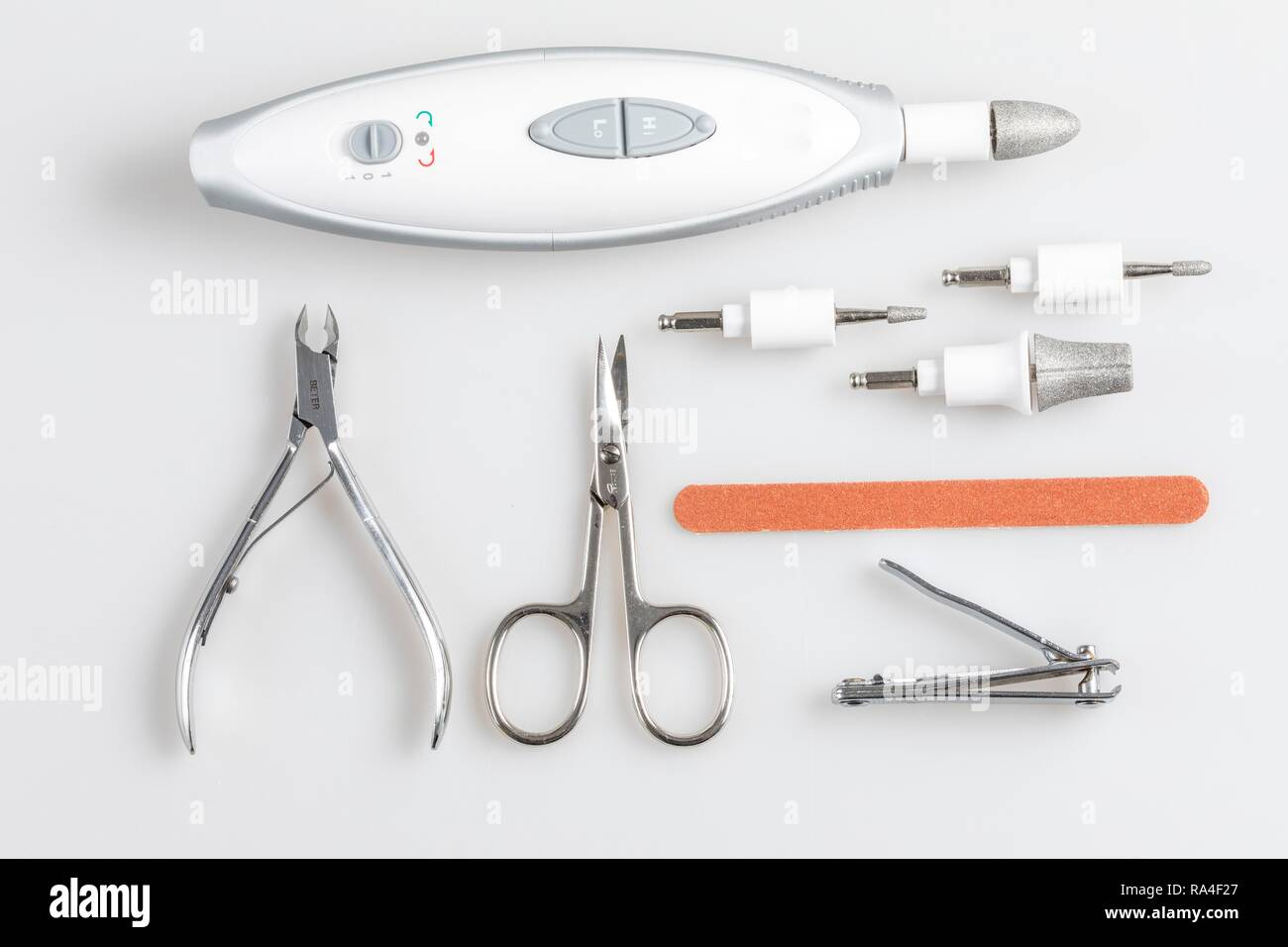 Nail care tools, nail clippers, nail scissors, nail pliers, electric nail file with various grinding heads - Stock Image