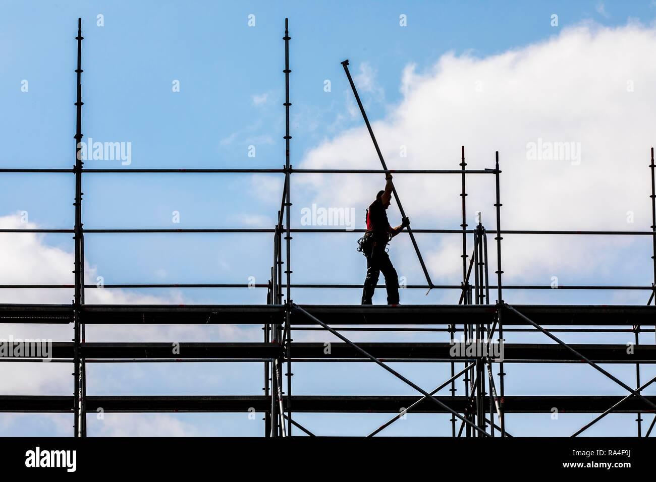 Gerüstbauer bei der Demontage eines großen, frei stehenden Baugerüst - Stock Image