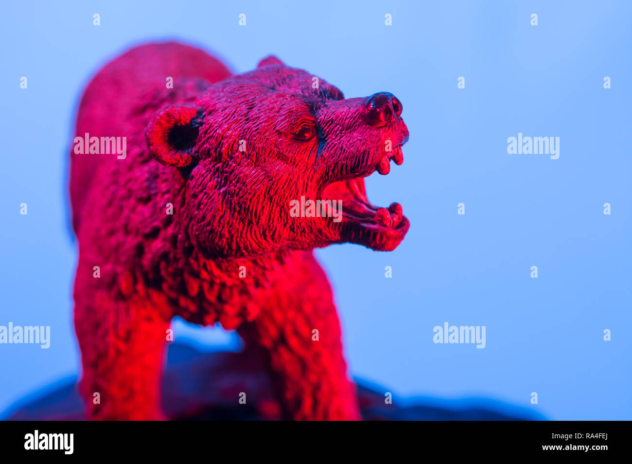 Toy bear standing on rock against plain background, all colour lit. Metaphor bear market, market bears, Stock Market bearish,being bearish. - Stock Image