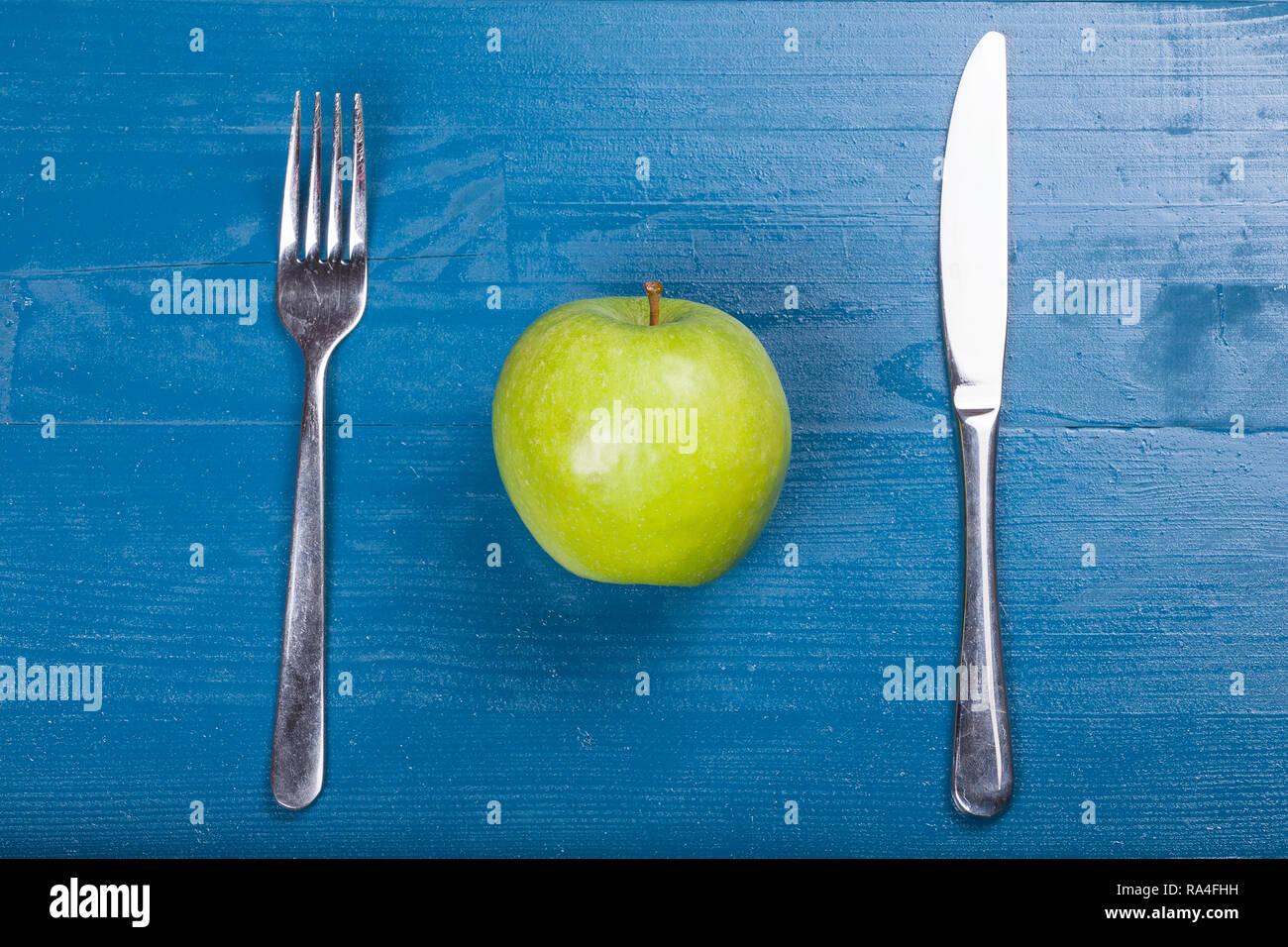 Vintage old cutlery knife fork green healthy apple blue wood background - Stock Image