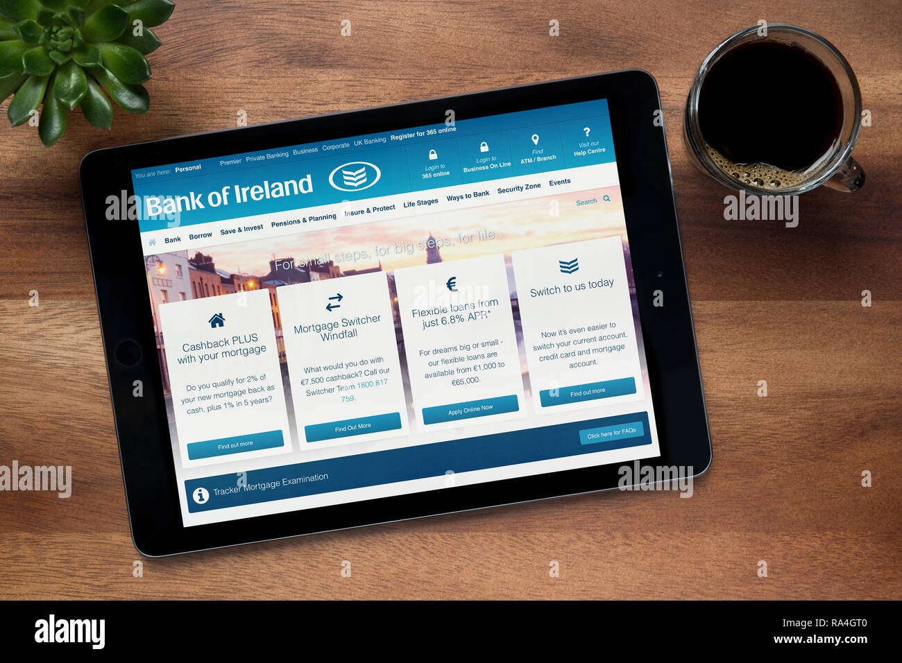 The website of Bank of Ireland is seen on an iPad tablet, on a wooden table along with an espresso coffee and a house plant (Editorial use only). - Stock Image