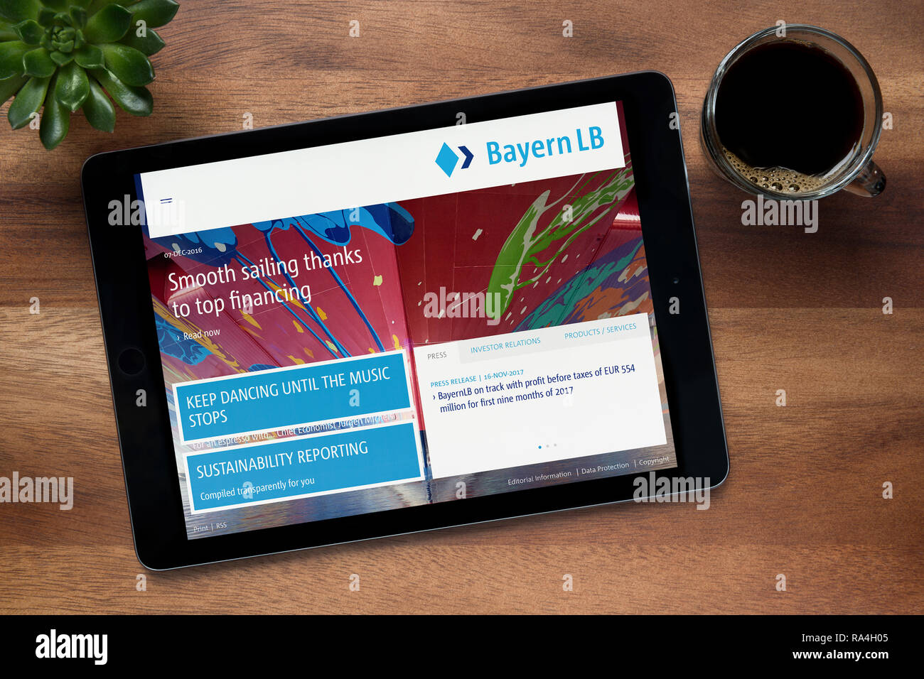 The website of Bayern LB is seen on an iPad tablet, on a wooden table along with an espresso coffee and a house plant (Editorial use only). - Stock Image