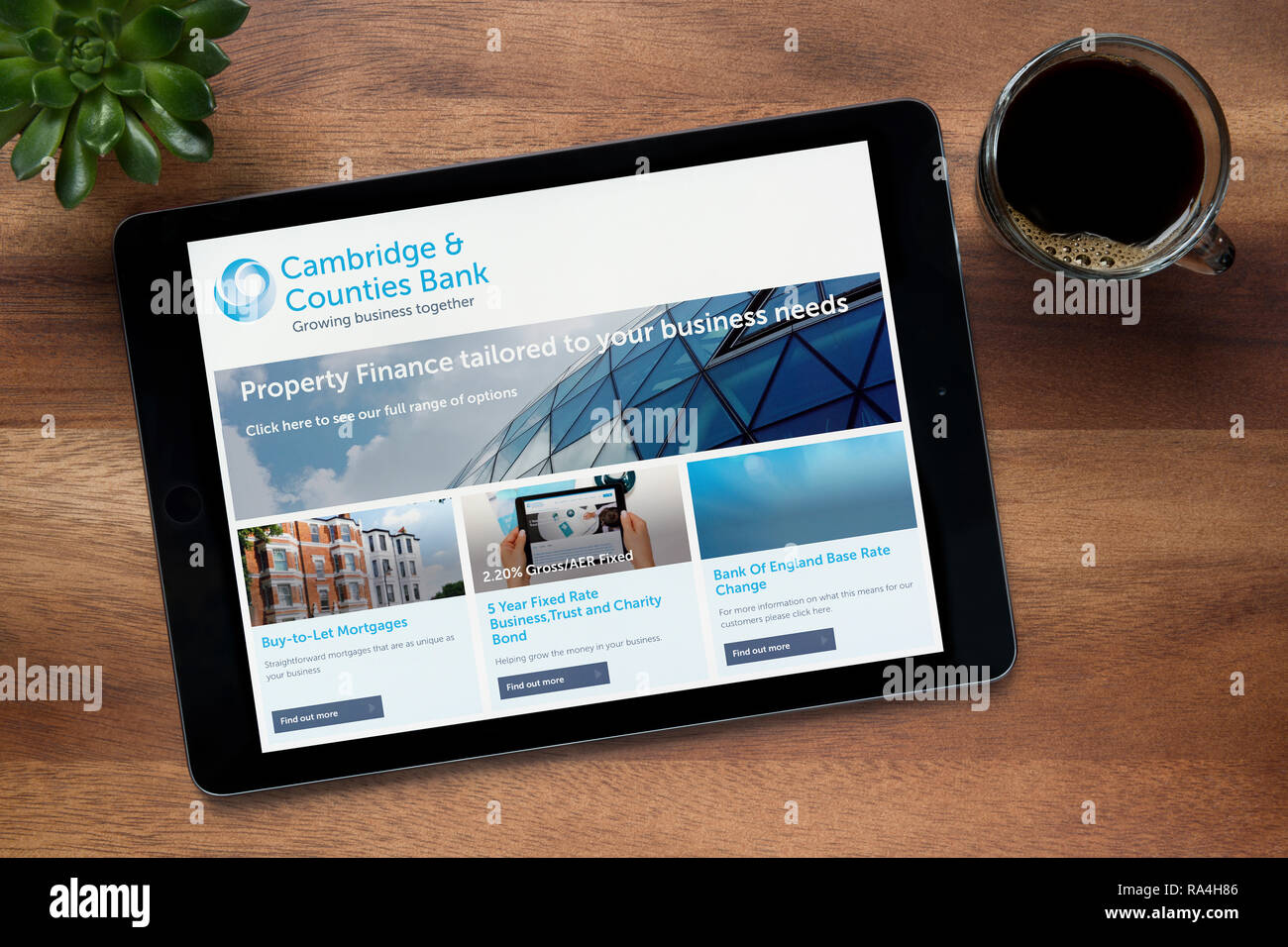 The website of Cambridge & Counties Bank is seen on an iPad tablet, on a wooden table  (Editorial use only). - Stock Image