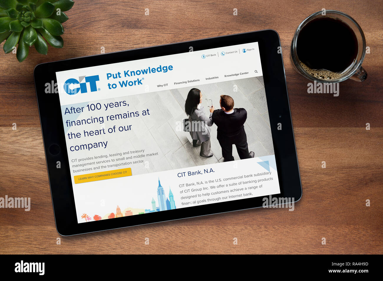 The website of CIT bank is seen on an iPad tablet, on a wooden table along with an espresso coffee and a house plant (Editorial use only). - Stock Image