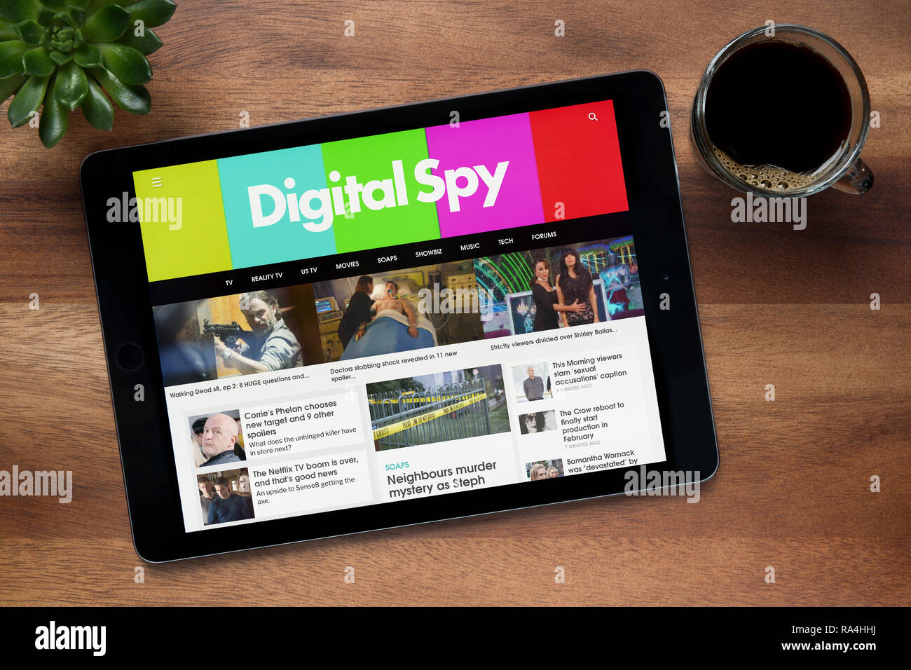 The website of Digital Spy is seen on an iPad tablet, on a wooden table along with an espresso coffee and a house plant (Editorial use only). - Stock Image