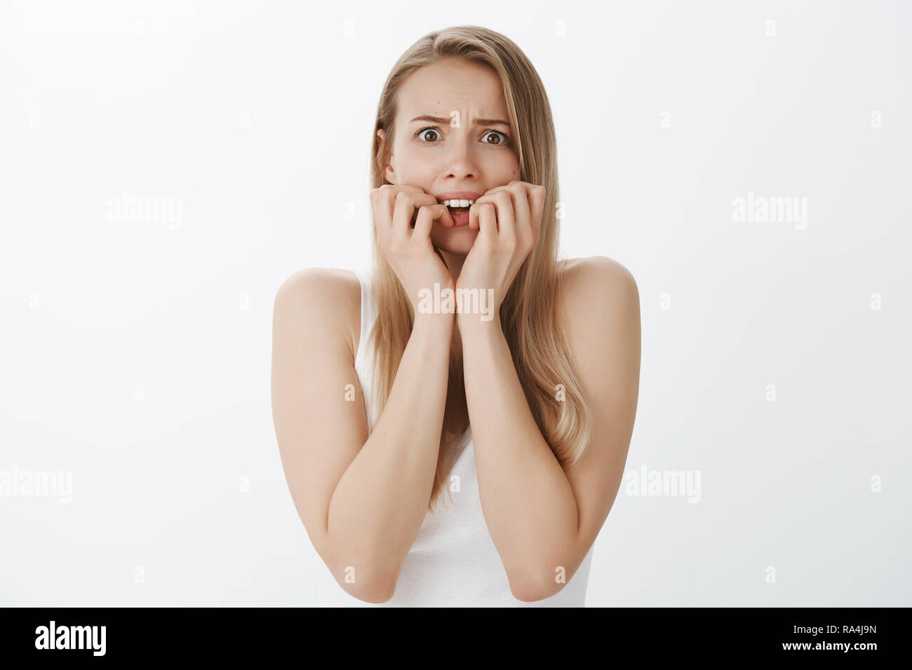 Waist-up shot of horrified panicking young insecure and attractive woman with blond hair and cute moles biting fingernails and frowning popping eyes at camera scared and timid over gray wall - Stock Image